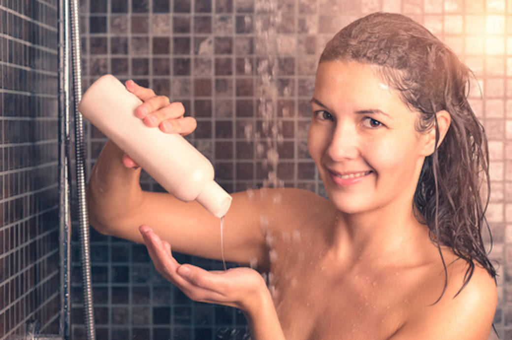 Junge Frau benutzt Shampoo