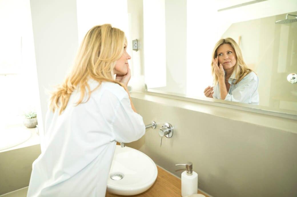 Frau schaut sich im Badezimmerspiegel an
