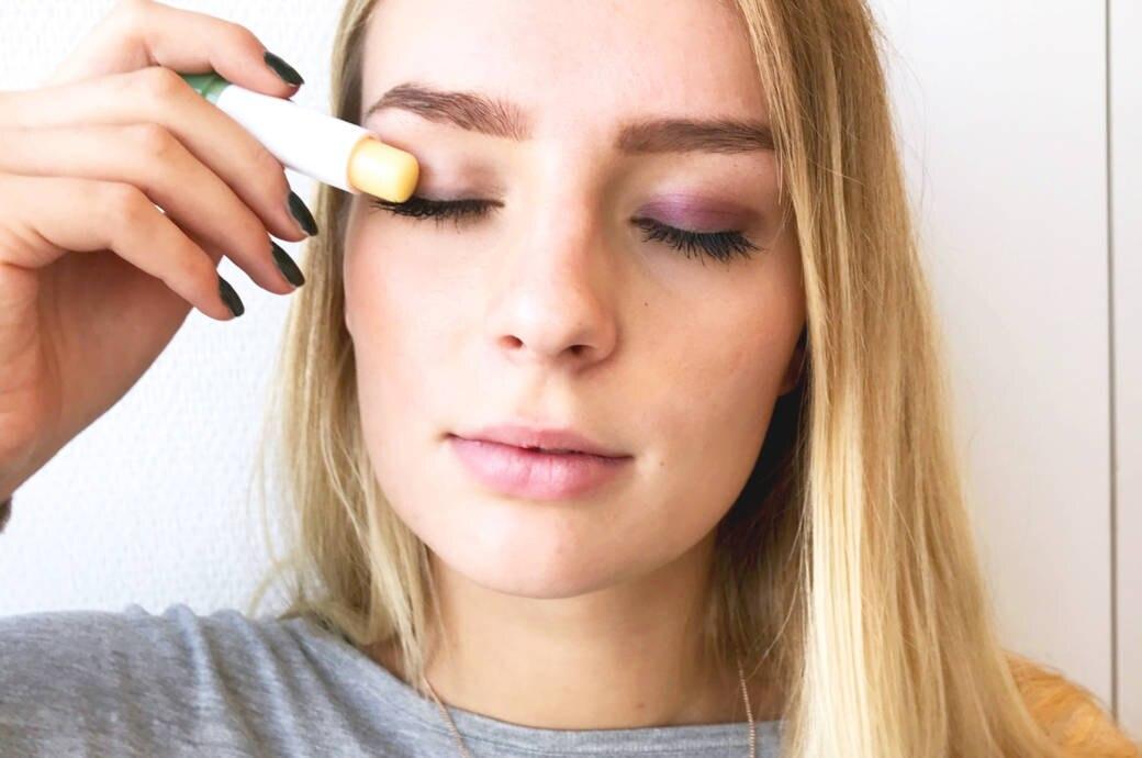 Junge Frau verwendet Lippenpflege als Lidschatten-Fixierer