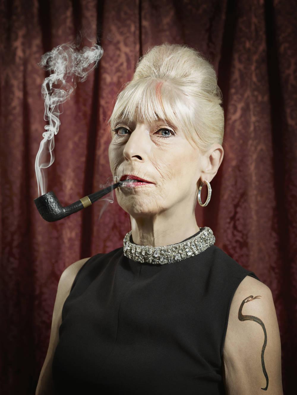 Eine rauchende ältere Dame, mit einer tätowierten Schlange auf der Schulter