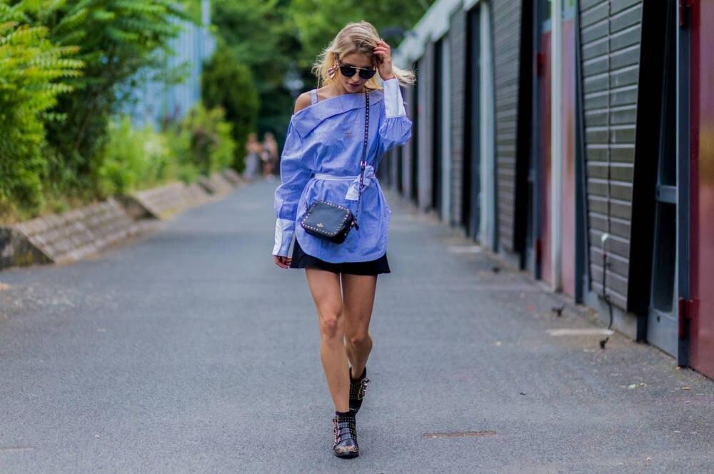 Caro Daur trägt hellblaue Bluse verkehrt herum
