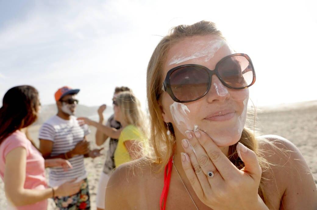 Frau cremt sich mit Sonnenschutz ein