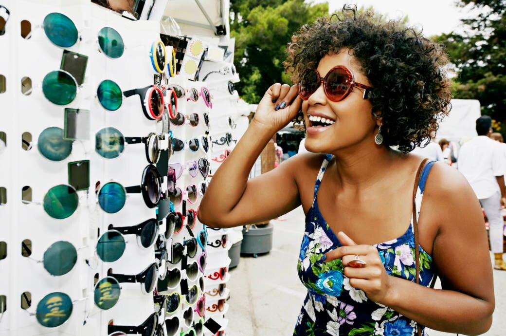 Lachende Frau probiert Sonnenbrille an
