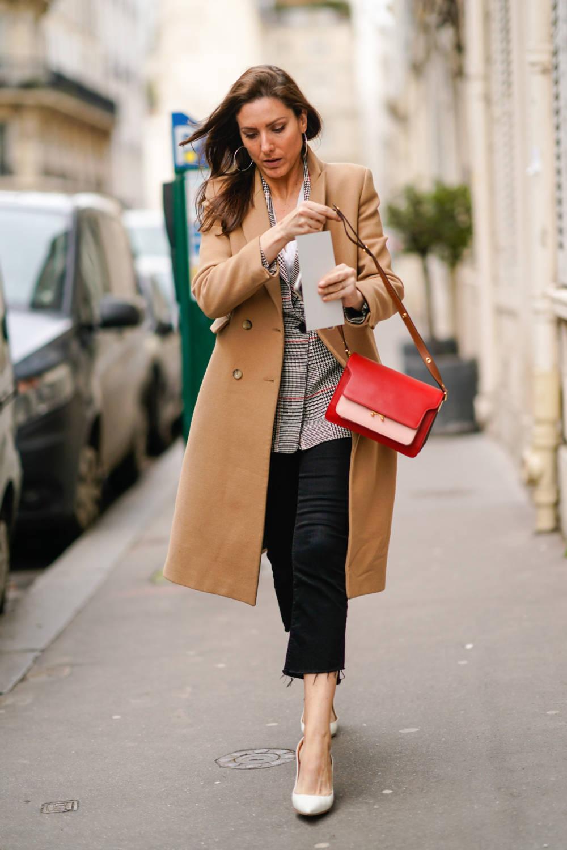 Frau trägt braunen Mantel und Cropped Jeans