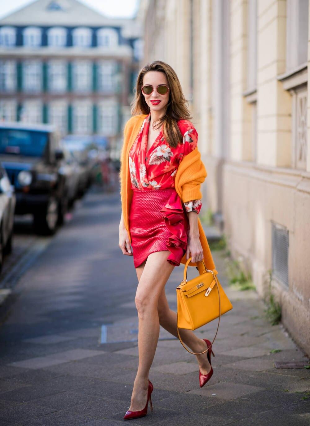 Frau trägt rotes Kleid und orangefarbene Accessoires