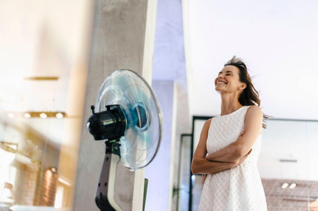 Frau steht vor einem Ventilator
