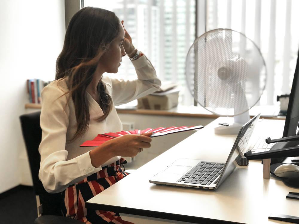 Frau im Büro mit Ventilator