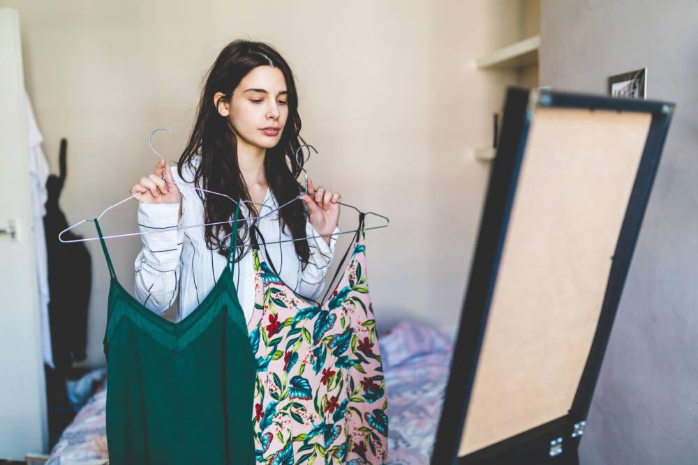 Unzufriedene Käuferin mit Kleidungsstück vor dem Spiegel