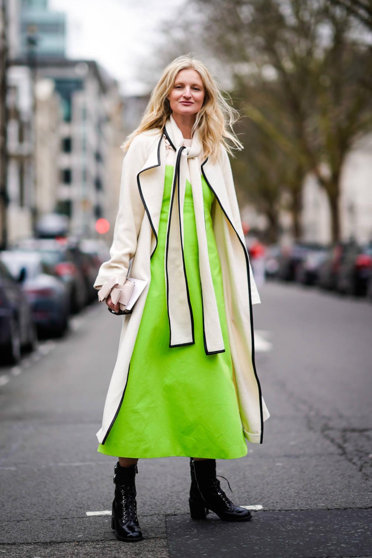Street Style Frau im neongrünen Kleid und Trenchcoat