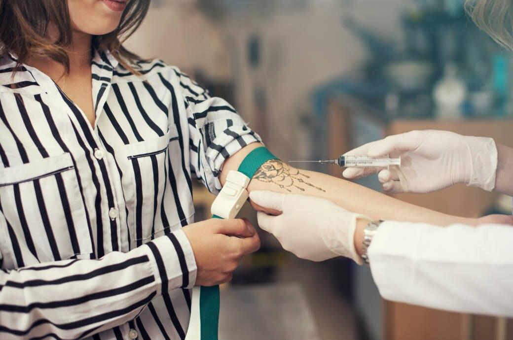 Frau mit Tattoo bei Blutabnahme