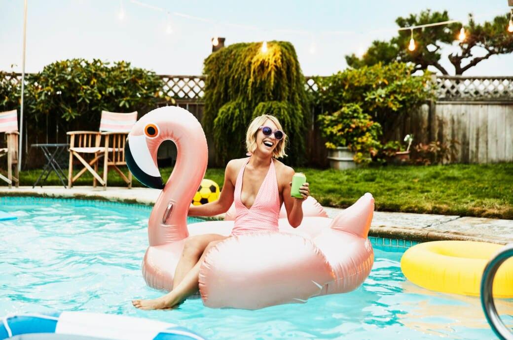 Frau mit Gummi-Flamingo im Pool