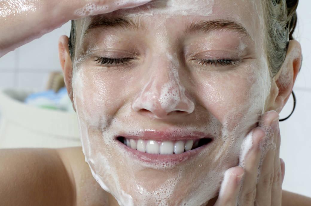 Junge Frau reinigt sich ihr Gesicht