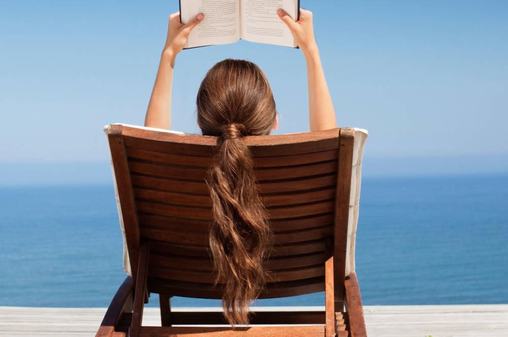 Frau mit Pferdeschwanz beim Lesen am Strand