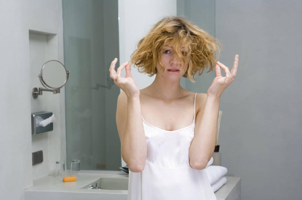 Frau mit zerzausten Haaren im Badezimmer
