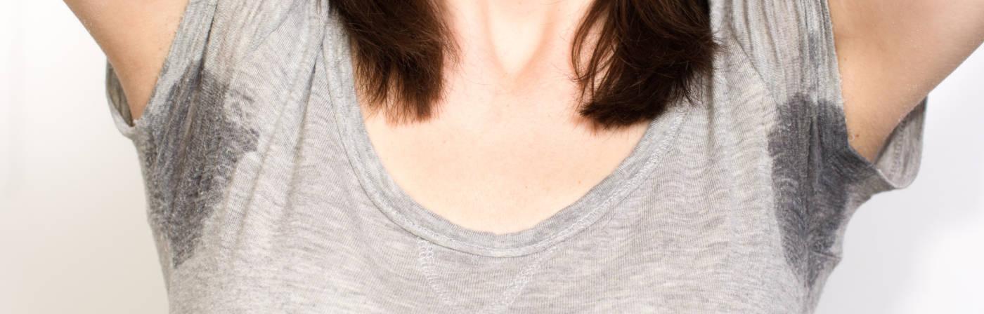 Frau mit Schweißflecken auf dem Shirt
