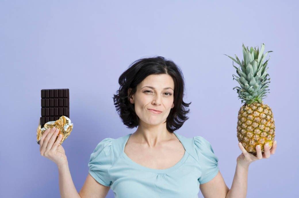 Frau mit Schokolade und Ananas in der Hand