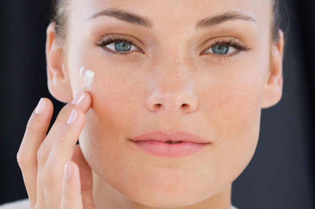 Junge Frau trägt Creme auf Gesichtshaut auf
