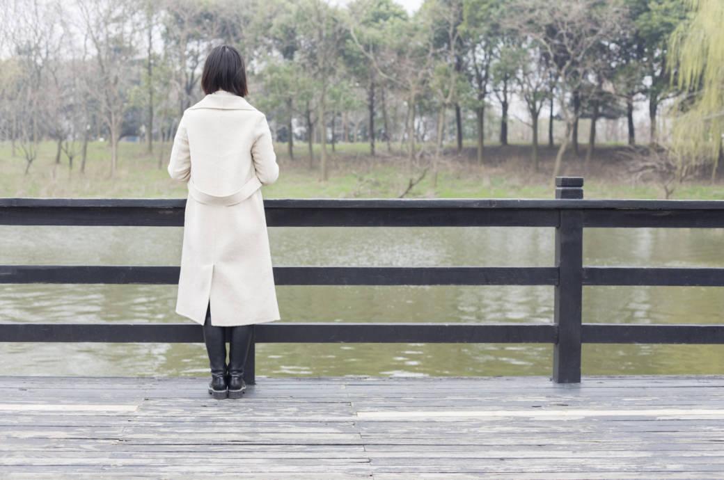 Frau im Mantel am Wasser