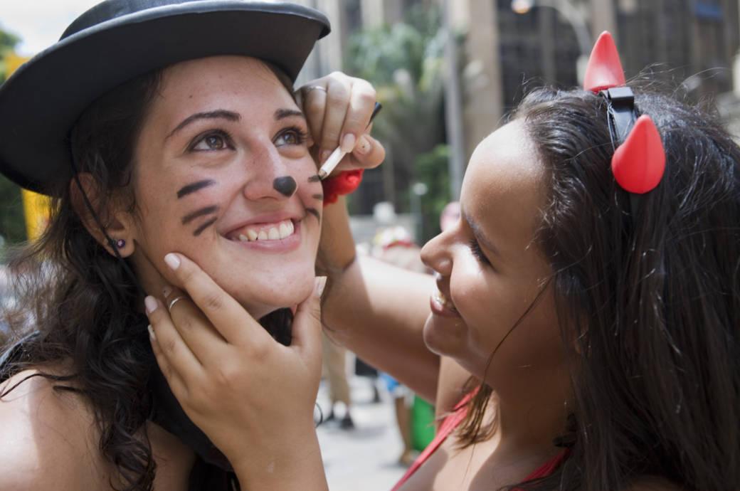 Frauen schminken sich für Karneval