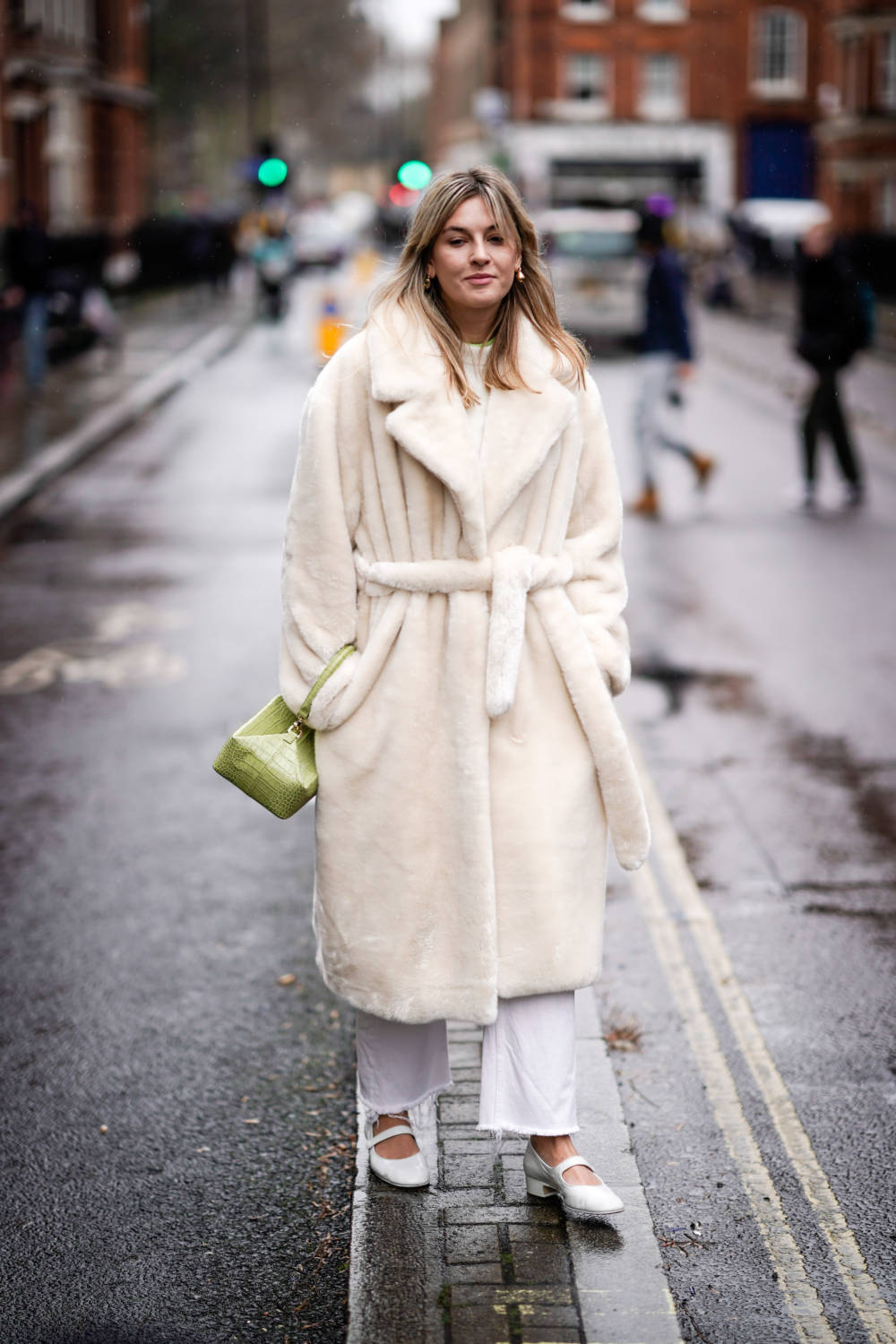 LONDON, ENGLAND - FEBRUARY 18: A guest wears earrings, a white fluffy coat, a lime green rectangular box bag, white pants, white ballerinas, during London Fashion Week February 2019 on February 18, 2019 in London, England. (Photo by Edward Berthelot/Getty Images)