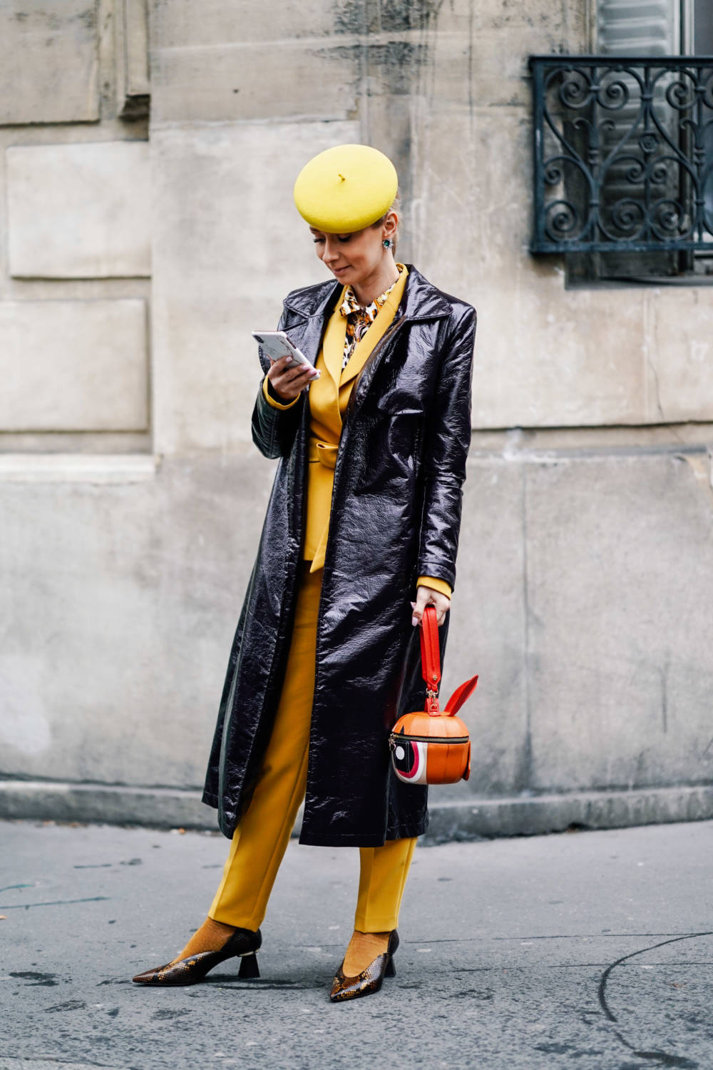 PARIS, FRANCE - MARCH 01: A guest wears a yellow beret hat, a yellow pantsuit, earrings, a shiny black vinyl raincoat, an orange-shaped handbag, a shiny golden python pattern pointy pumps with fantasy heels, yellow socks , outside Issey Miyake, during Paris Fashion Week Womenswear Fall/Winter 2019/2020, on March 01, 2019 in Paris, France. (Photo by Edward Berthelot/Getty Images)