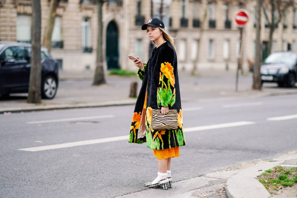 PARIS, FRANCE - FEBRUARY 28: A guest wears a NY black cap, a black fluffy coat with yellow,orange and green daffodils design, an orange dress, a yellow and black zebra pattern bag, white openwork socks, deep green and white gingham slingback pumps, outside Atlein, during Paris Fashion Week Womenswear Fall/Winter 2019/2020, on February 28, 2019 in Paris, France. (Photo by Edward Berthelot/Getty Images)