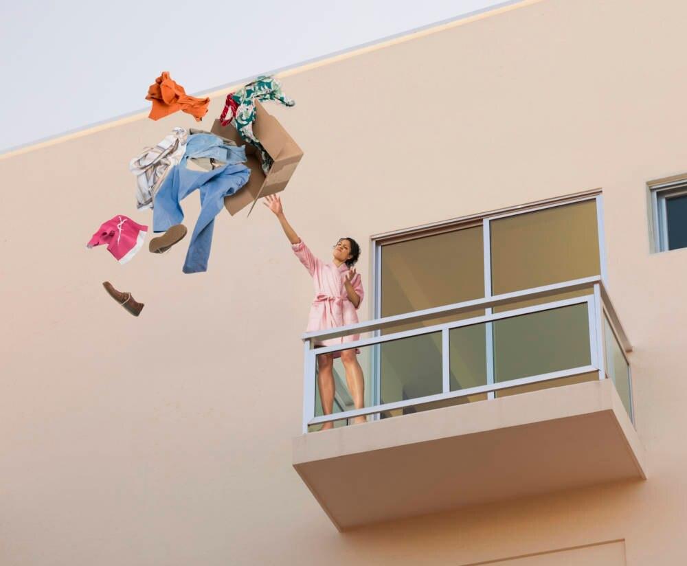 Frau wirft Kleidung aus Fenster