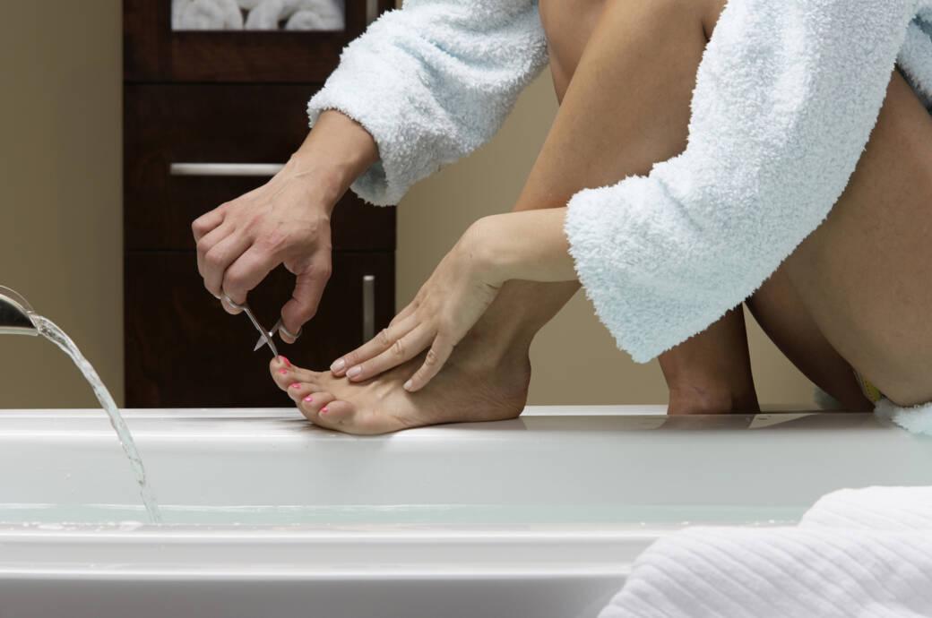 Frau, die ihre Füße pflegt
