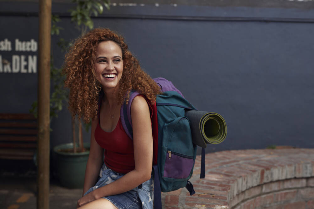 Young woman with backpack smiling, while sitting in courtyard