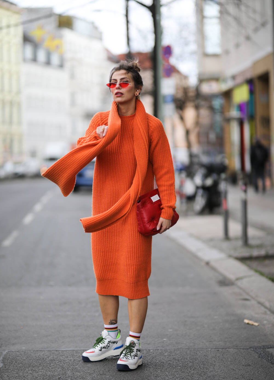 Frau in orangefarbenem Look mit Schal