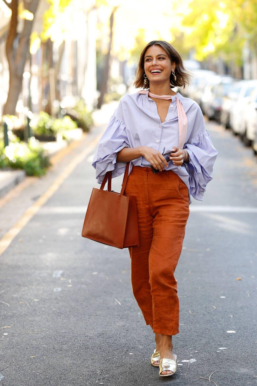 Frau mit fliederfarbener Bluse zu rostroter Hose