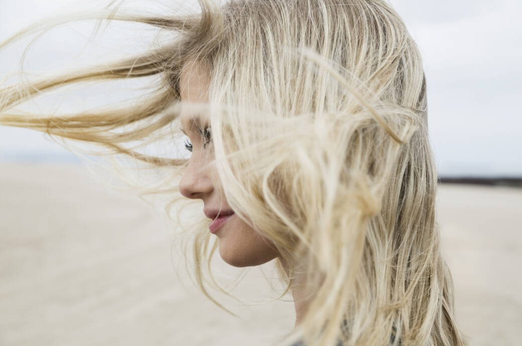 Frau mit blondem Haar am Strand