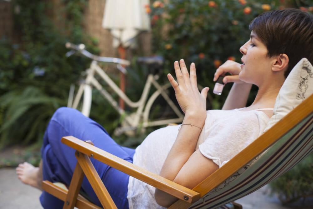 Schwangere Frau lackiert Nägel
