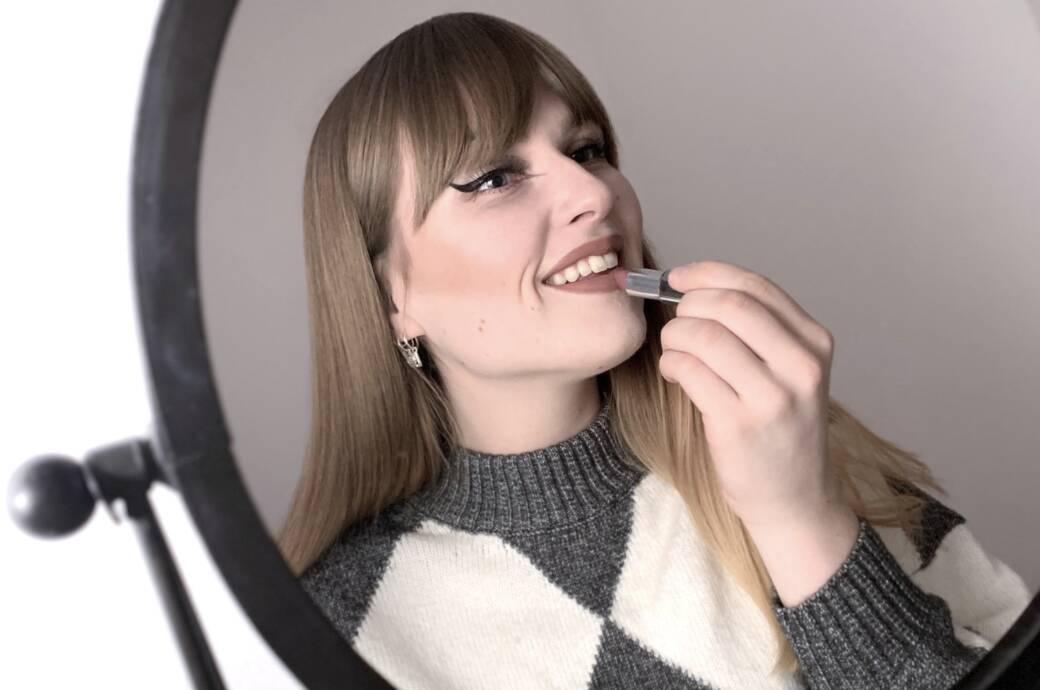 Frau die Lippenstift aufträgt