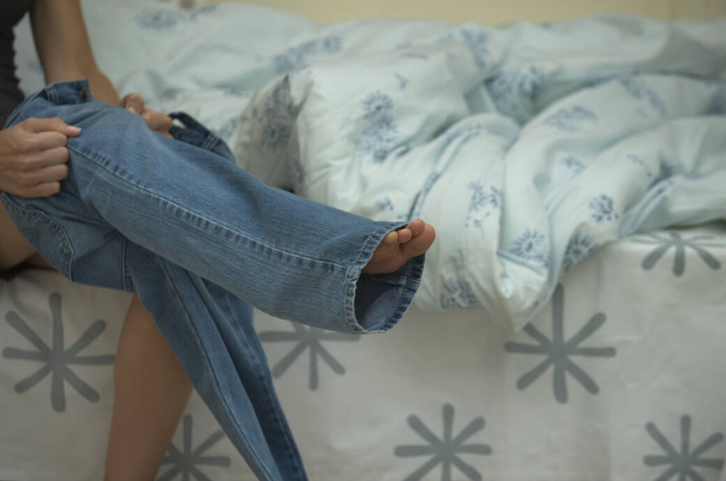 Frau, die sich eine Jeans anzieht