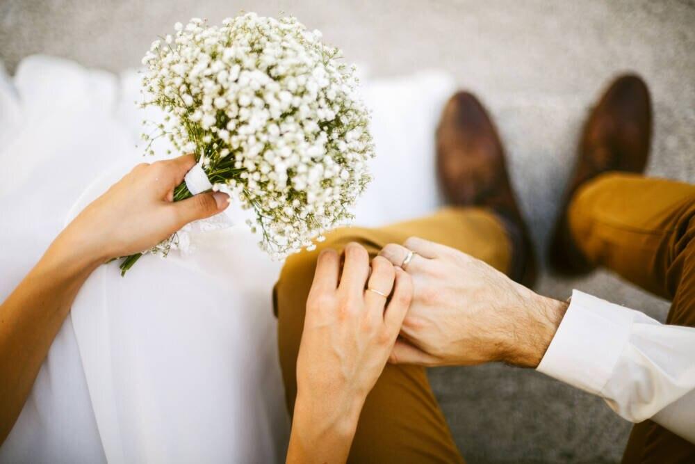 Brautpaar mit Blumen und Eheringen