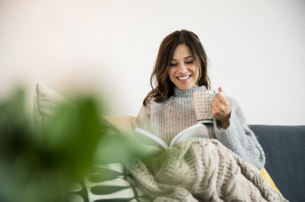 Hygge: Frau sitzt auf Sofa mit Decke und Tee
