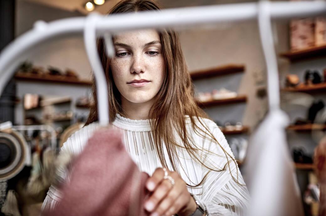 Frau vor Kleiderstange