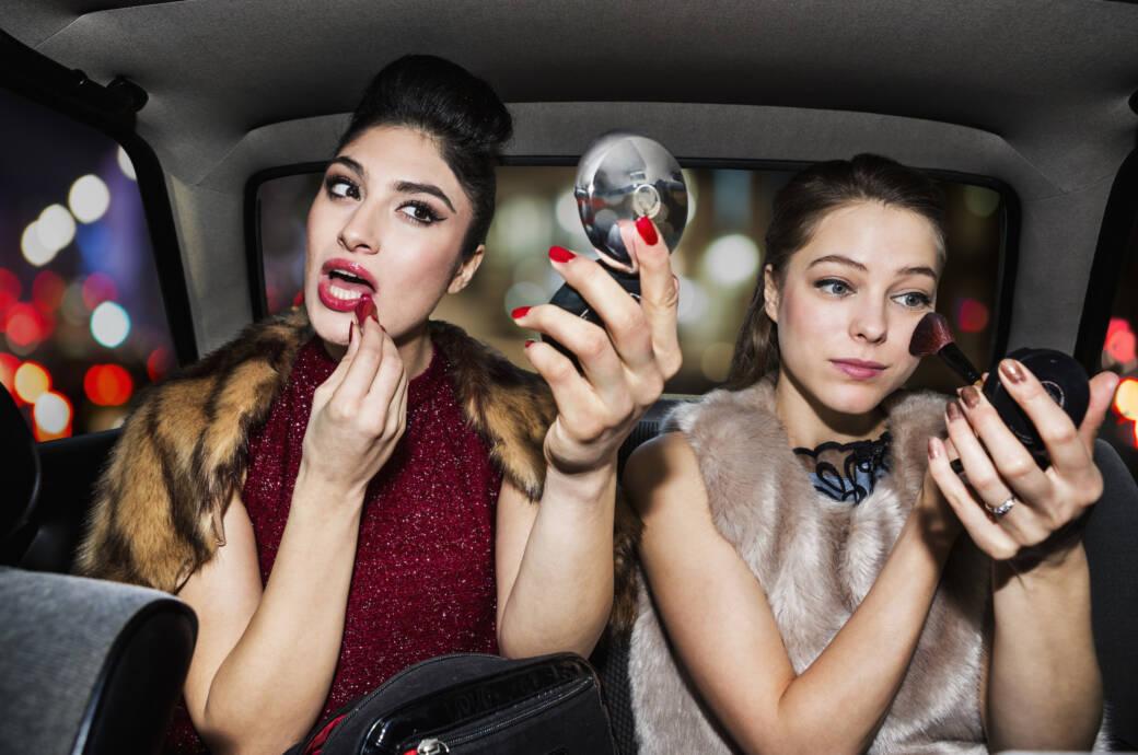 Zwei Frauen schminken sich im Auto