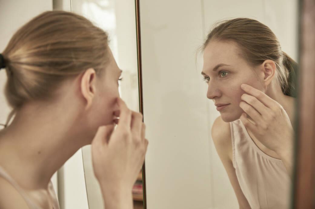 Frau mit Milien im Gesicht