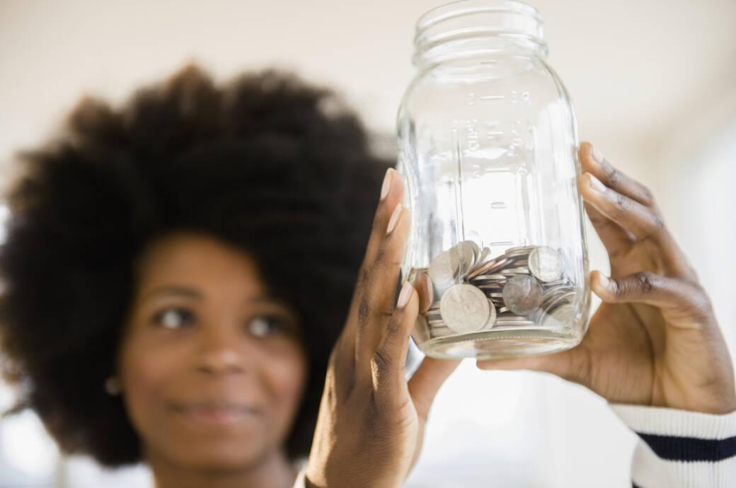 Frau, die eine Geldbüchse in der Hand hält