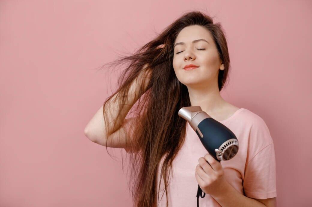 Frau, die sich die Haare föhnt