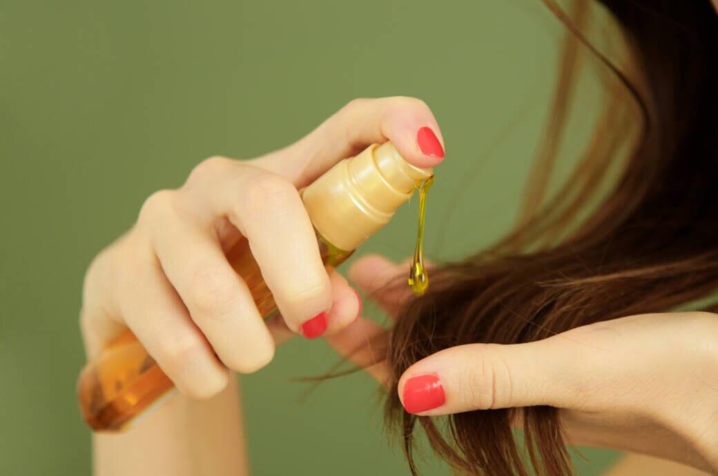 Frau, die sich Haaröl in die Spitzen schmiert