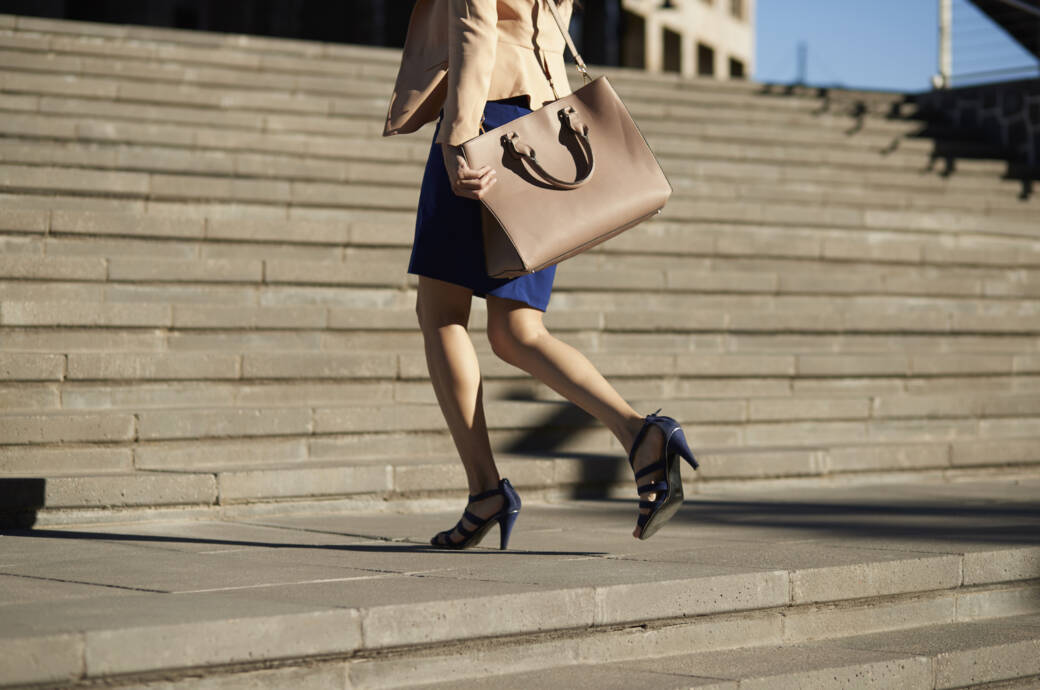 Frau mit großer, schwerer Handtasche