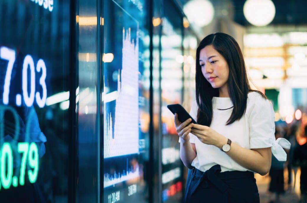 Frau mit Smartphone vor Börsenkurs