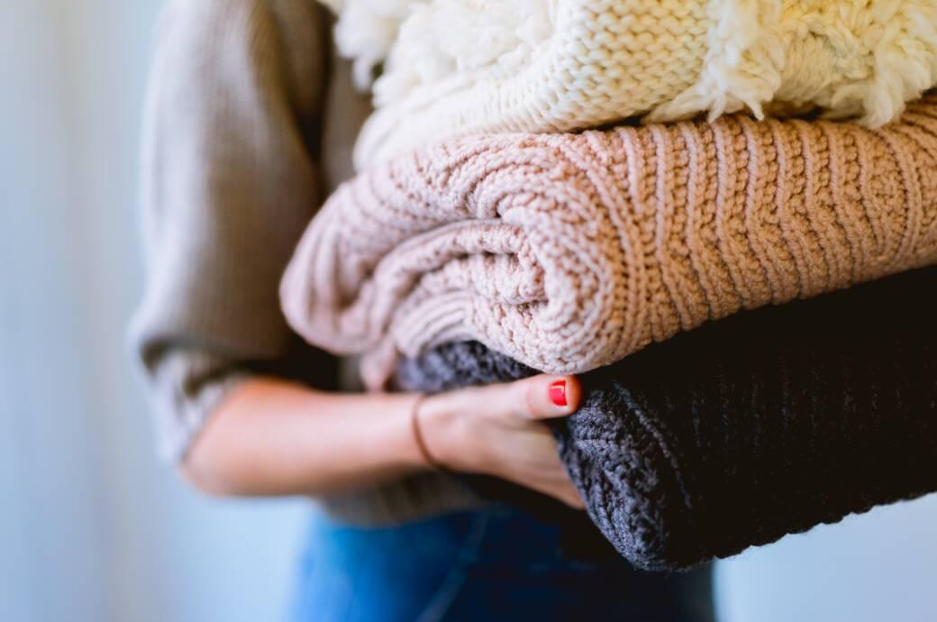 Frau mit Pullovern in der hand